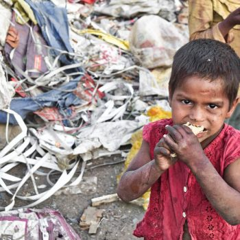 Ein essender Junge in einem Slum