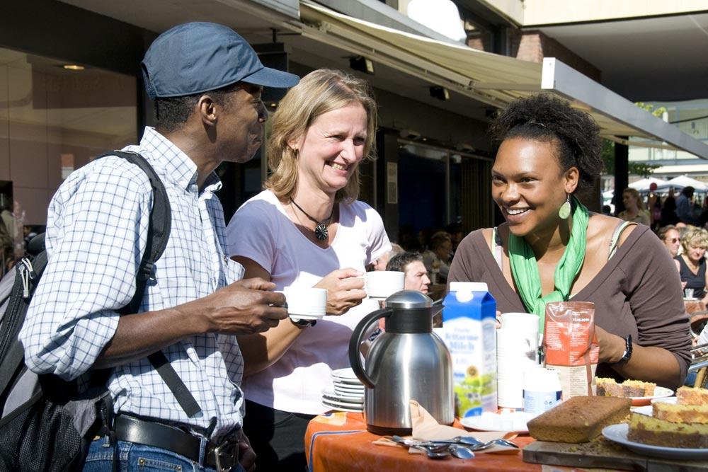 Drei lachende Menschen an einem Kaffeetisch. (Foto: Presseamt Münster / Angelika Klauser)